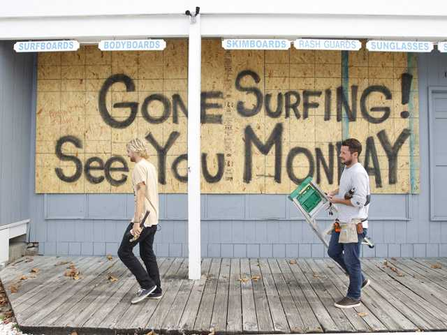 Store workers Fletcher Birch, right, and Jay Kleman finish boarding up the windows on a surf store in Ocean City, Md. on Saturday.