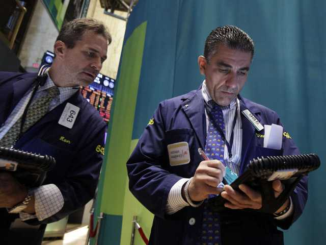 Traders Ronald Madarasz, left, and Vincent Quinones work on the floor of the New York Stock Exchange.