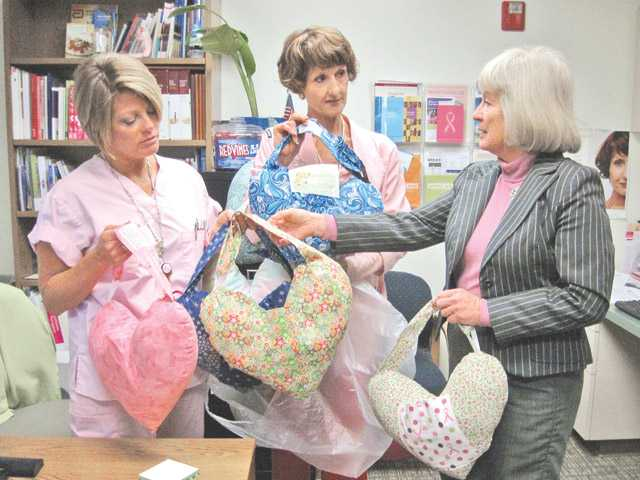 Zontian Suzie Alziebler, right, delivers Huggy Heartz pillows to patient navigators at the Sheila R. Veloz Breast Imaging Center Mindy Burgess and Colleen Shaffer, who will distribute the pillows to breast cancer patients to ease post-surgery discomfort.