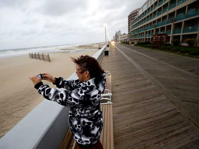 Mary Corrus if Ocean City, Md., takes a picture of the rough surf as Hurricane Sandy bears down on the East Coast Sunday in Ocean City.