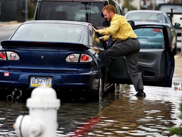 Cody Billotte loads his car to go to work as Hurricane Sandy bears down on the Ocean City, Md., and the rest of the East Coast on Sunday.