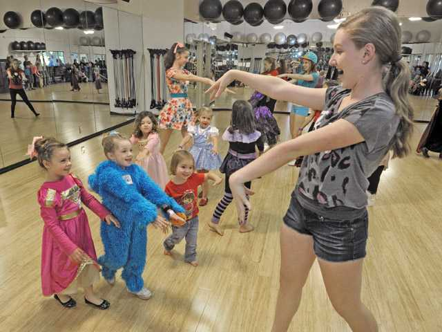 "Hart High School dance team members Haley Leffin, rear, and Marie-Claire Meadows, right,  teach kids the steps to ""Thriller"" at the YMCA Harvest Festival in Valencia on Saturday."