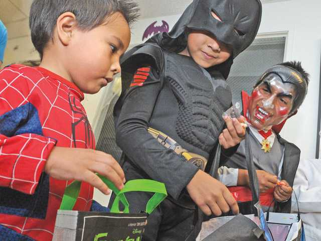 From left, A.J. Montes-DeOca, 4, brother Avi, 9, and Mark Lopez, 7, compare the candy they gathered trick-or-treating.