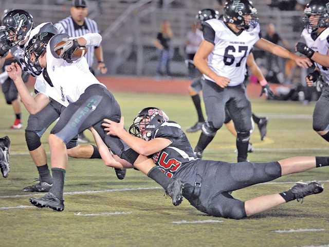 SCCS's Colton Huckabone (25) drags down Fairmont Prep quarterback Bobby Varnadoe (4), holding Fairmont to a loss on fourth down, giving the ball to SCCS at Canyon High School on Saturday.