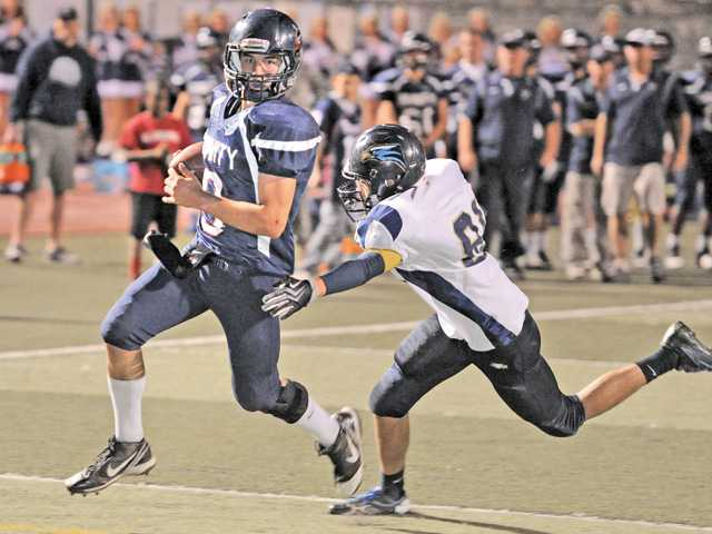 Trinity Classical Academy's Dakota Prochnow (9) evades Lancaster Baptist's Josh Allen (81) at College of the Canyons on Saturday.