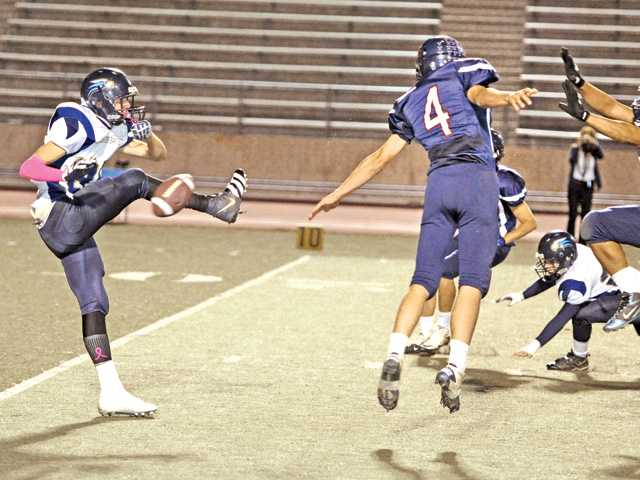 Trinity's Spencer Klehn (4) blocks a Lancaster Baptist punt by Aaron Blaszczyk (85) in the first quarter to set up a Trinity touchdown at COC on Saturday.