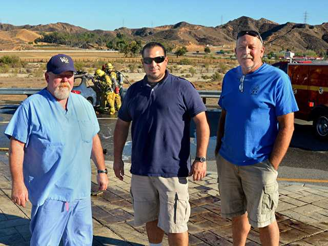 From left, Floyd Buchan, of Castaic, Andres Gamero, of Castaic, and John Springer, of Canyon Country, are seen at the Hasley Canyon exit off the northbound Interstate 5 in Castaic on Sunday. (Rick McClure/For The Signal)