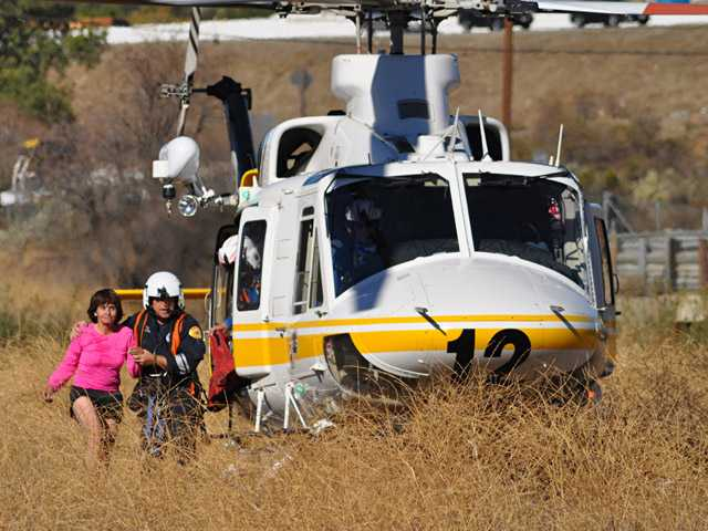 A Los Angeles County Fire Department Air Squad member escorts a hiker away from the helicopter in Towsley Canyon on Sunday. (Rick McClure/For The Signal)