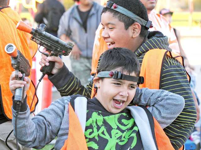 Sixth-graders Jovany Gonzales, 12, foreground, and Daniel Castillo, 11, enjoy a game of laser tag at the Harvest Festival at Leona Cox Community School in Canyon Country on Thursday.