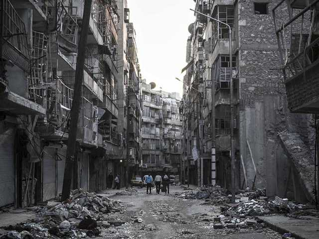 In this Saturday photo, Syrian residents walk on a street among the debris of buildings damaged by heavy shelling in Aleppo City.