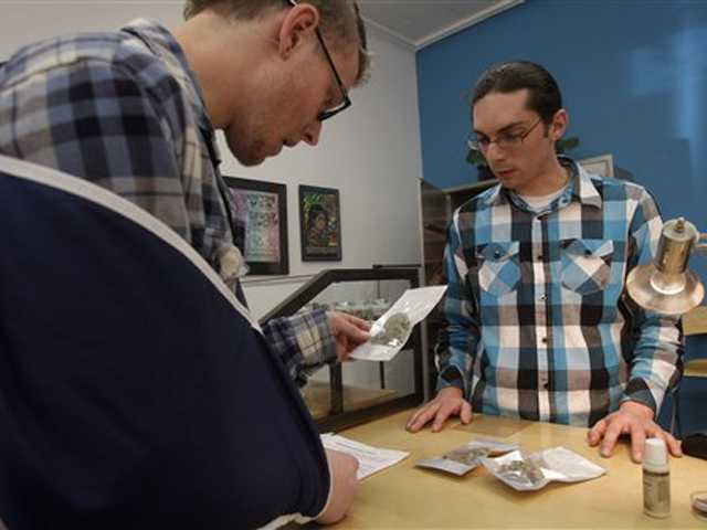Medical marijuana patient Douglas Klann, left, is shown bags of marijuana by clerk Jason Matthys at Harborside Health Center in Oakland, Calif., on Feb. 1.