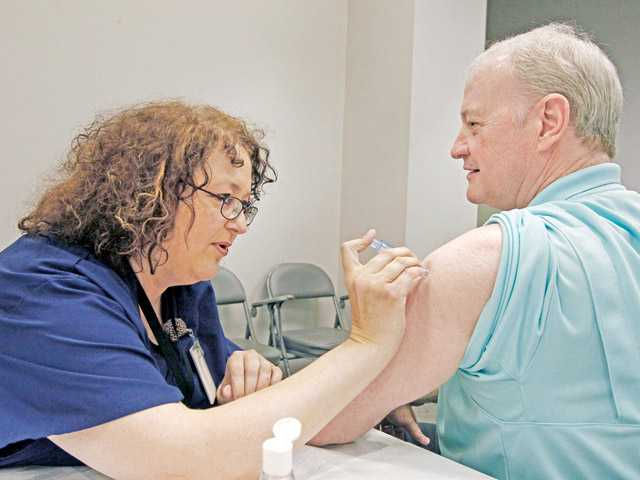 Bill Staples, a Mississippi Department of Health employee, is given an intradermal shot (pictured far right) of flu vaccine by nurse Rosemary Jones also with the health department Oct. 17 in Jackson, Miss.