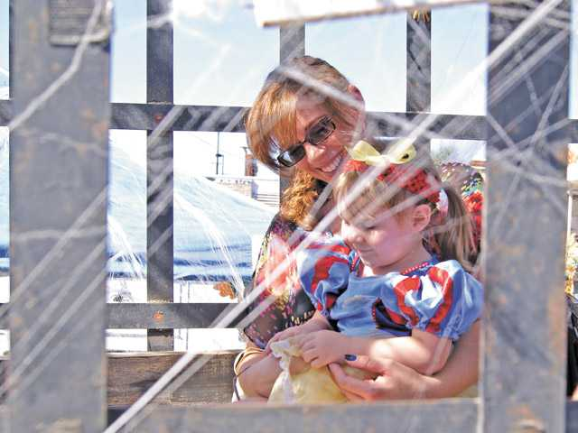 Christina Golding and her princess-clad daughter Melanie, 2, enjoy a fun time inside the sheriff's prisoner wagon Sunday at the Haunted Jailhouse Halloween Carnival.
