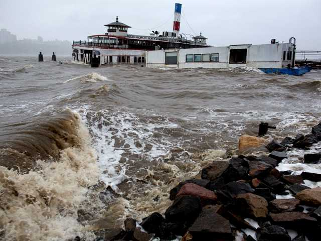 The Hudson River swells and rises over the banks of the Hoboken, N.J., waterfront as Hurricane Sandy approaches on Monday, Oct. 29, 2012.