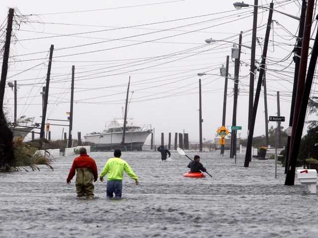 People wade and paddle down a flooded street as Hurricane Sandy approaches, Monday, Oct. 29 in Lindenhurst, N.Y. Gaining speed and power through the day, the storm knocked out electricity to more than 1 million people.