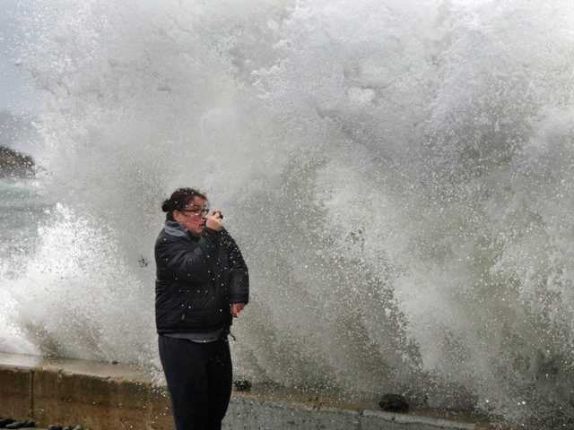 Lisa Famularo braces for impact as a large wave crashes over a seawall while she photographed heavy surf in the Atlantic Ocean during the early stages of Hurricane Sandy, Monday, in Kennebunk, Maine.
