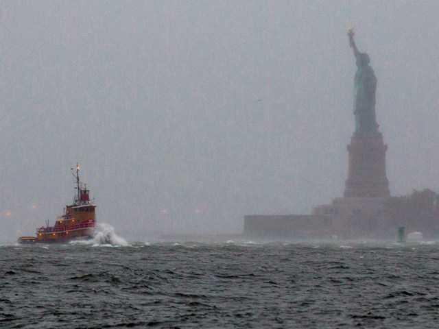 Waves crash over the bow of a tug boat as it passes near the Statue of Liberty in New York Monday, as Hurricane Sandy churned the waters of New York Harbor.