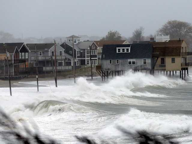 Ocean waves kick up near homes along Peggoty Beach in Scituate, Mass. Monday