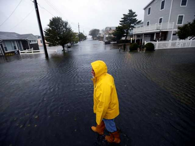 Al Daisey walks in the flood water in front of his home as Hurricane Sandy bears down on the East Coast, Monday, in Fenwick Island, Del.