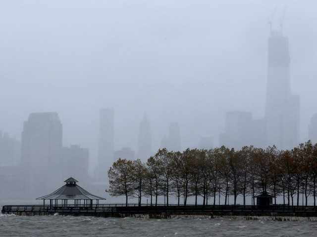 One World Trade Center, right, peeks through a light rain as water from the Hudson River creeps up on Pier A Park with the expected arrival of Hurricane Sandy in Hoboken, N.J., Monday, Oct. 29, 2012.