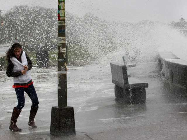 A woman reacts to waves crashing over a seawall in Narragansett, R.I., Monday.