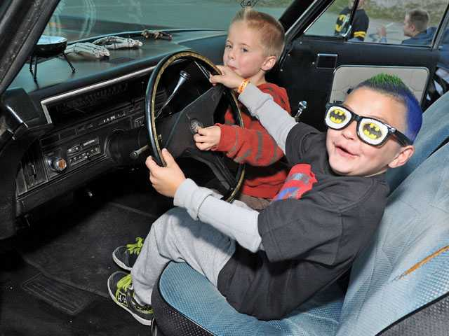 Kindergartners Austin Onkst, left, and Wyatt Lowry, both 5, check out a hearse parked at the Harvest Festival at Leona Cox Community School in Canyon Country on Thursday.