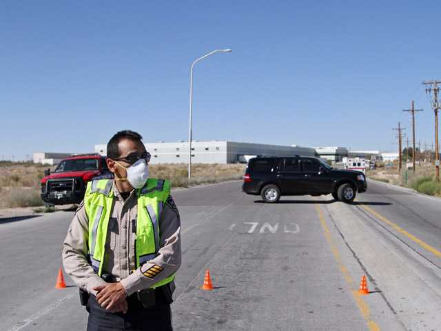 A police officer blocks an intersection outside the Santa Teresa Industrial Park in Santa Teresa, N.M. on Tuesday.