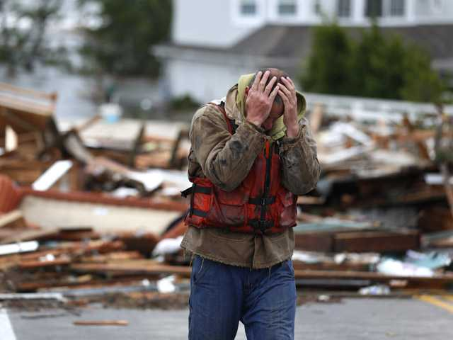 Brian Hajeski, of Brick, N.J., reacts after looking at debris of a home that washed up on to the Mantoloking Bridge after superstorm Sandy rolled through.