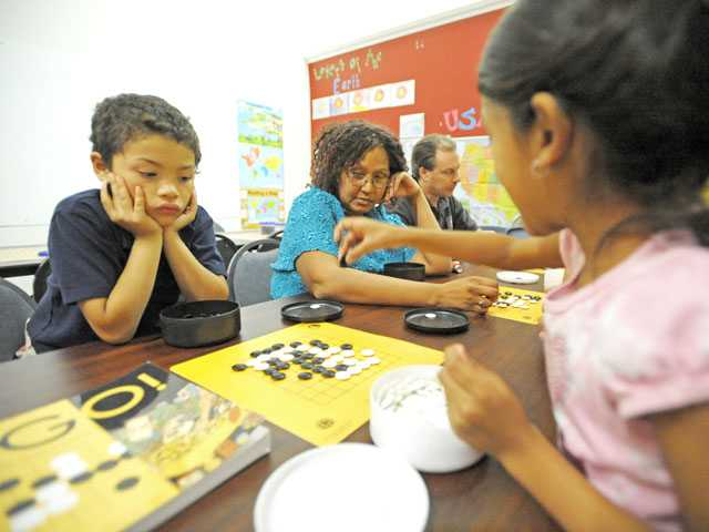 From left, Isaiah Anschultz, 7, and his mother Sharon watch as Shriya Rajesh, 7, makes a move in the game of Go.