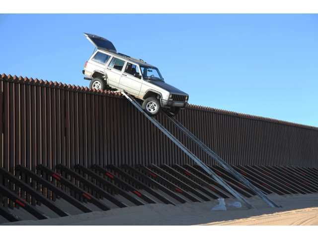 A silver Jeep Cherokee that suspected smugglers were attempting to drive over the U.S.-Mexico border fence is stuck at the top of a makeshift ramp early Wednesday, near Yuma, Ariz.