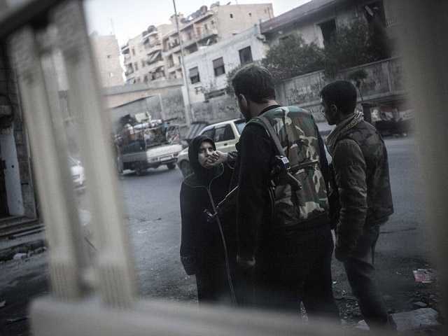 In this Tuesday photo, a Syrian woman is stopped and questioned by rebels at a checkpoint in the Bustan Al-Pasha neighborhood.