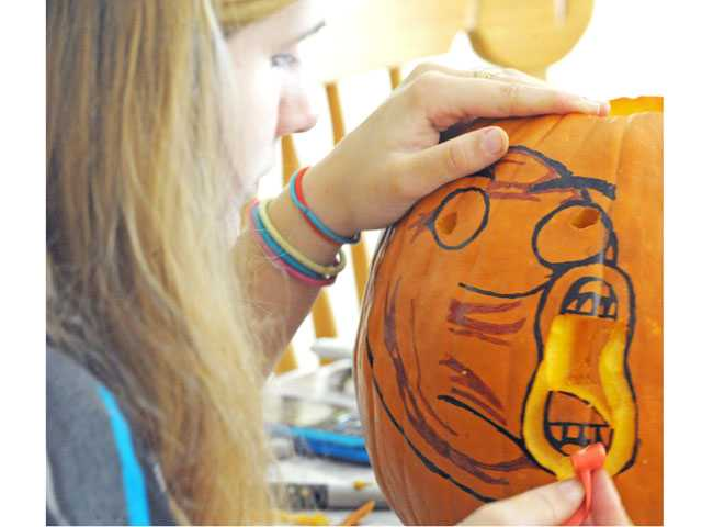 Becky Hanney, 16, carves pumpkins in her Saugus home on Monday.