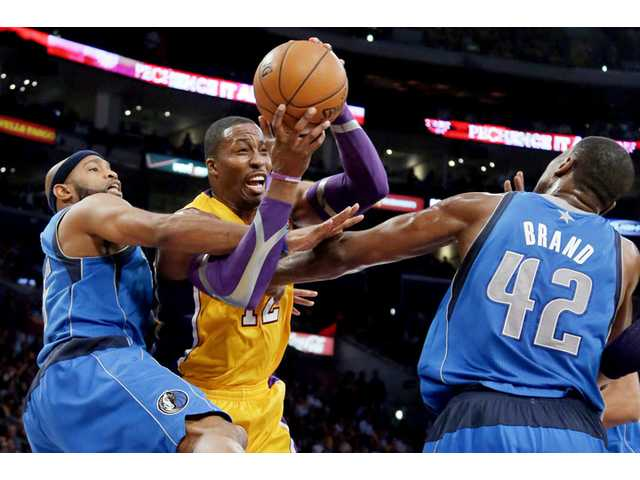 Los Angeles Lakers Dwight Howard, center, is defended by Dallas Mavericks Vince Carter, left, and Elton Brand on Tuesday in Los Angeles.