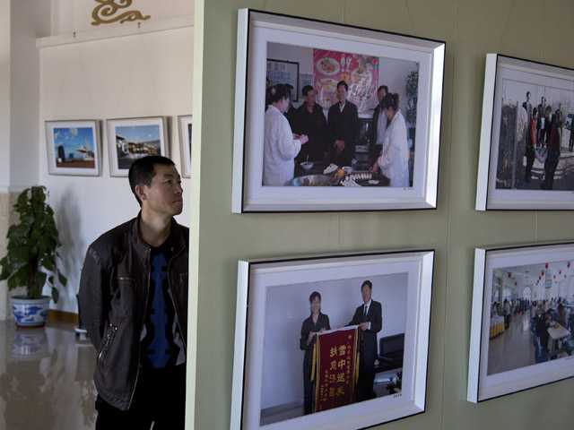 A man tours a photo exhibition showing the government officers' activities and coal mining for the upcoming 18th national congress.