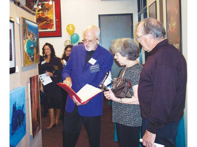 Photographer Bruce McFarland, center, shows Marsha and Dale McLean his portfolio of his photographs that he has converted into paintings. He also explained the technical process of the photographs' transformation.