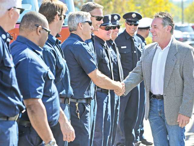 Retiring Los Angeles County Fire Department Assistant Chief Bill Niccum, right, shakes hands with the firefighters from four local L.A. County fire companies as they turned out to send him off from the Jan Heidt Newhall Metrolink Train Station on Niccum's last day on Wednesday.