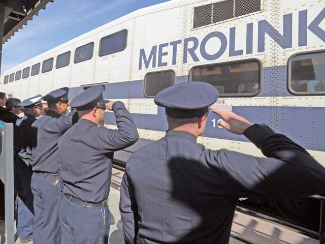 L.A. County Firefighters salute the Metrolin train carring retiring Niccum as he leaves the Jan Heidt Newhall Metrolink Train Station on Wednesday.