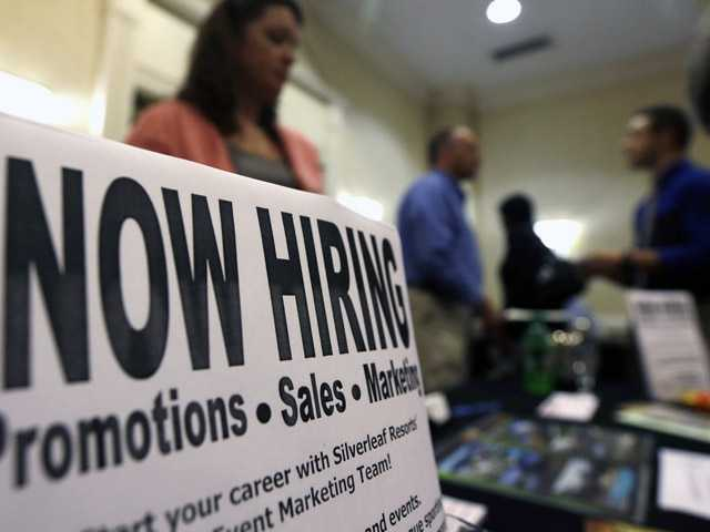 In this Thursday photo, a sign attracts job-seekers during a job fair at the Marriott Hotel in Colonie, N.Y.