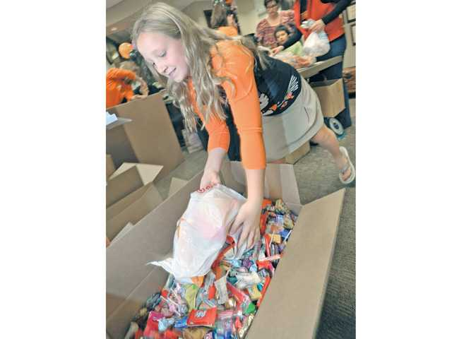 Kameron Smudde dumps some of the hundreds of pounds of donated Halloween candy into boxes at the Operation Gratitude Event held at Gateway Dental Suites in Valencia on Thursday.