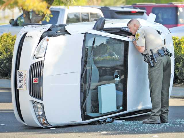 A Santa Clarita Valley sheriff's deputy looks inside a Saturn coupe that overturned at the corner of Grandview Drive and Newhall Ranch Road on Friday afternoon. No injuries were reported. Signal photo by Dan Watson.