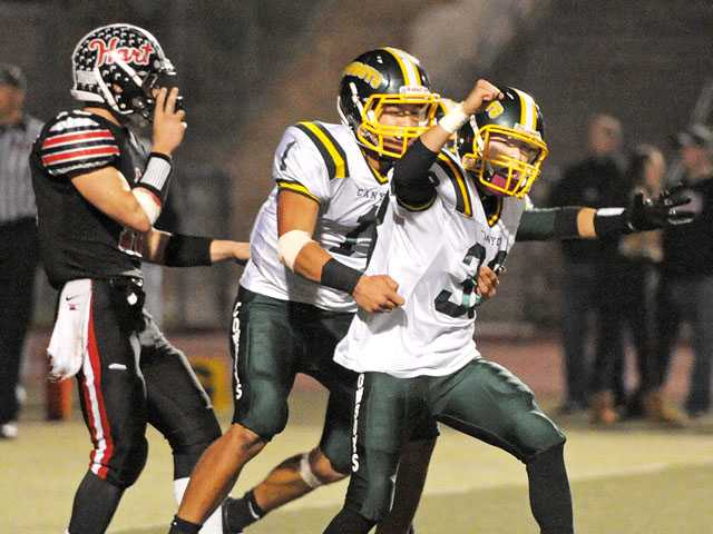Canyon quarterback Cade Apsay (1) and kicker Bonifacio Rojas celebrate Rojas' 17-yard, game-winning field goal against Hart on Friday night at College of the Canyons.
