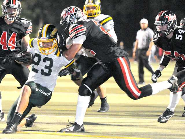 Canyon's Myron McAfee (23) drives the ball to the 1-yard line as Hart defensive back Justus Delgado makes the stop on Friday night at College of the Canyons.