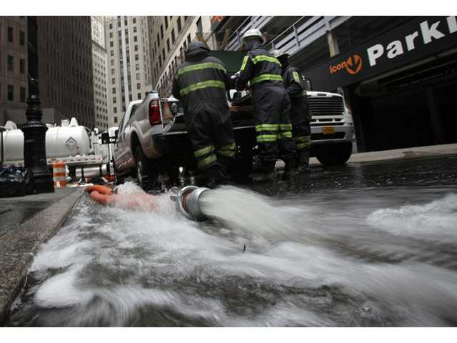 Water is pumped from a subterranean parking garage in New York's Financial District, Friday.