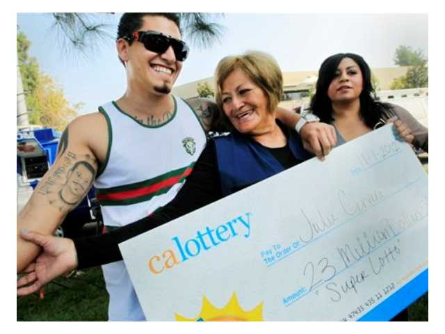 Lottery winner Julie Cervera, center, looks at her recently dead son pictured on a tattoo, as she is hugged by her grandson Rudy Ray, left, and daughter Charliena Marquez, right, after a news conference Friday, Nov. 2, 2012. The 69-year-old California grandmother came forward to claim a $23 million lottery jackpot after the winning ticket had almost expired.