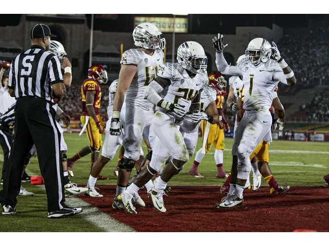 Oregon running back Kenjon Barner (24) celebrates scoring a touchdown during the second half of an NCAA college football game against the Southern California on Saturday in Los Angeles. Oregon won 62-51.