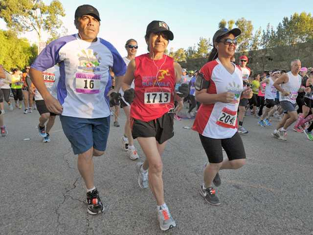From left, Armen Anassian, Clara Pentreath and Leni Calma make their way down McBean Parkway to start the Santa Clarita Marathon in Valencia on Sunday.