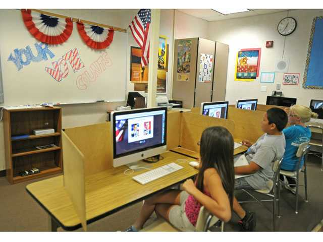 Students use computers to cast their votes in the mock presidential election. Schools across the Santa Clarita Valley and the state participated.