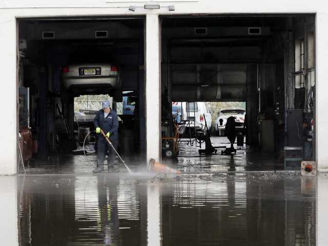 Steve Formica washes a garage bay at Chizzy's Truck and Auto Repairs in the wake of superstorm Sandy on Thursday in Little Ferry, N.J.