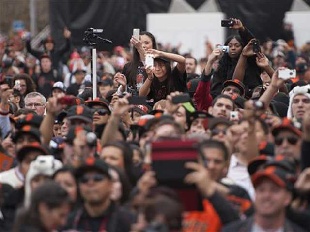 San Francisco Giants fans take photos of their team at City Hall, following a parade in celebration of the team's victory in the baseball World Series, on Oct. 31 in San Francisco.