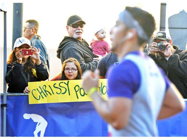 Alyssa Guerrero, 10, holds a sign as her brother Chris Guerrero, foreground, approaches the finish line.